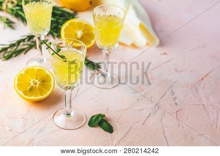 Traditional Italian Homemade Lemon Alcohol Drink Liqueur Limoncello With Pieces Of Lemon And Rosemar