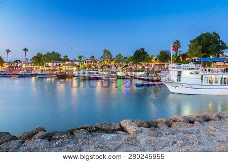 Side, Turkey - June 8, 2018: The harbour with boats in Side at night, Turkey. Side  is an ancient Greek city on the southern Mediterranean coast of Turkey.