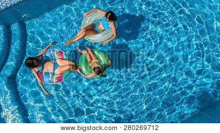 Family In Swimming Pool Aerial Drone View From Above, Happy Mother And Kids Swim On Inflatable Ring