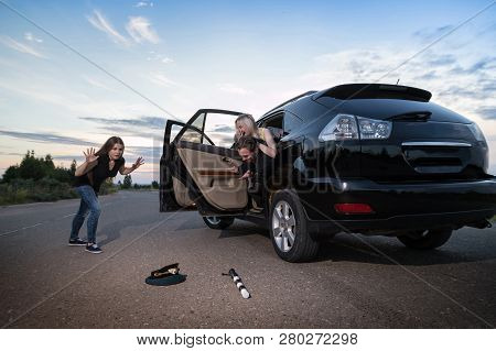 Friends In The Car Looking With Horror At The Cap And Baton Of A Police Officer On The Road. Female