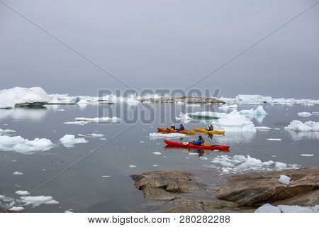 Ilulissat, Greenland - July 1, 2018: Group Of People Kayaking In Between Icebergs At Ilulissat Icefj
