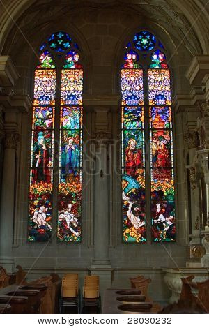 Bright multi-colour stained-glass windows in an ancient cathedral in Switzerland