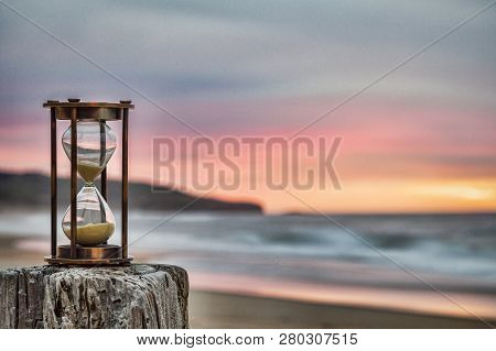 Hourglass Outdoors Standing On Jetty Post With Moody Sunrise Sky.