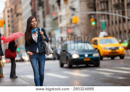 Young Asian professional woman walking home commuting from work in New York city street. Urban people lifestyle commuter in NYC traffic rain day. Chinese girl with purse and headphones for commute.