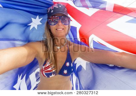 Proudly Australian Woman Bears The Australian Flag On Her Hat, Sunglasses And Bikini While Holding A