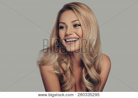 Proud Of Her Perfect Hair. Beautiful Young Woman Smiling And Looking Away While Standing Against Gre