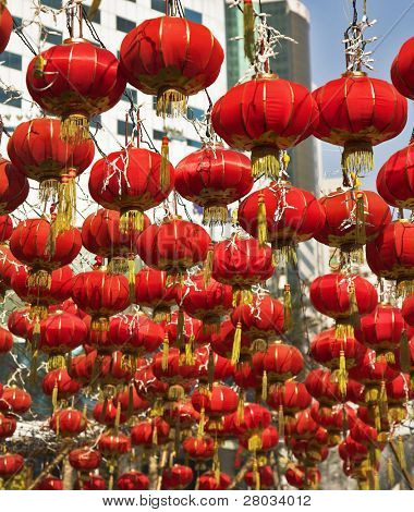 The traditional red lanterns decorating modern skyscrapers, in the Chinese city in New year