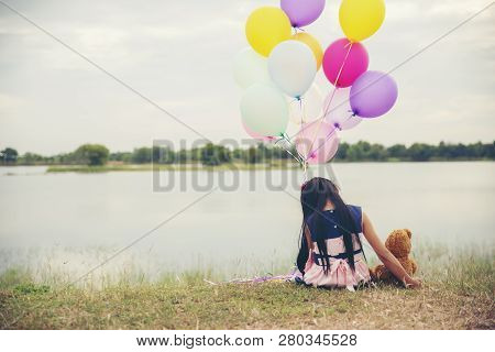Sad Child With Family Problem,hugging Teddy Bear And Holding Balloon In Park.asian Little Girl Sitti