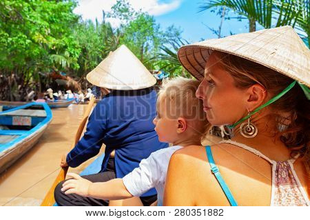 Happy Family Ride On Traditional Vietnamese Boat By Yellow Brown Water In Canal. Mekong River Delta