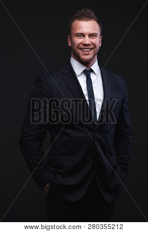 Closeup Studio Portrait Of Young Handsome Smiling Businessman Isolated On Dark Studio Background