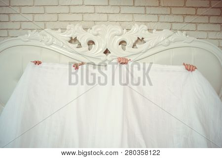 A Funny Married Couple, Lying In Bed And Hiding Under A White Blanket, Only Arms Are Visible. Fun In