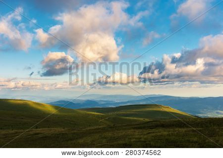 Wonderful Evening Landscape. Beautiful View From The Grassy Hill In To The Distant Valley And Mounta