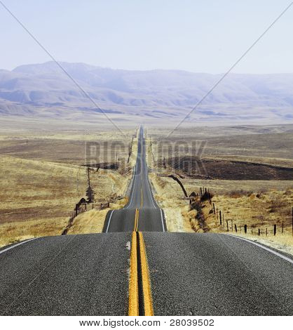 The Californian prairie and mountains in the distance, autumn day. Magnificent American road and fencing
