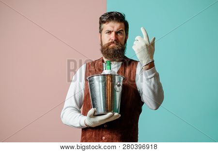 Butler With Ice Bucket With Champagne Bottle. Waiter In High Class Restaurant Serving Wine Or Champa