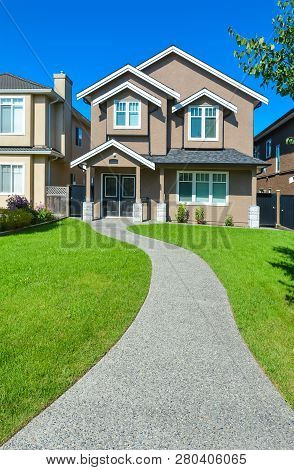 New House With Concrete Pathway Over Front Yard Lawn. Small Family House In Vancouver, British Colum