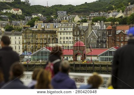 Tourists On A Ferry In Oban Harbor Looking Back Toward The City