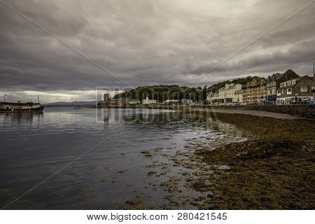 Oban Harbor In Scotland At Sunrise With Grey Sky