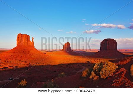 Famous mittens of red sandstone on the background of blue sky and light clouds. Sunset poster