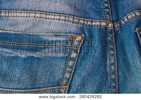 Blank Real Leather Jeans Label Sewed On Old Worn Blue Jeans. Denim Background, Jeans, Closeup Surfac