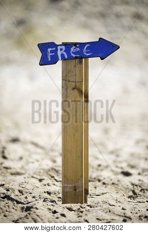 Free Sign Fixed On Wooden Stick In The Sand