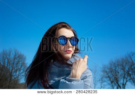 Outdoor Portrait Of Young Girl Wearing Mirrored Blue Sunglasses And Winter Clothes Posing On Bright