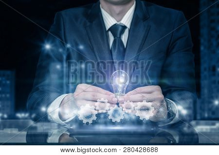 A Businessman Is Sitting At The Table And Holding An Idea Symbol Lightbulb With Cogwheel Mechanism U