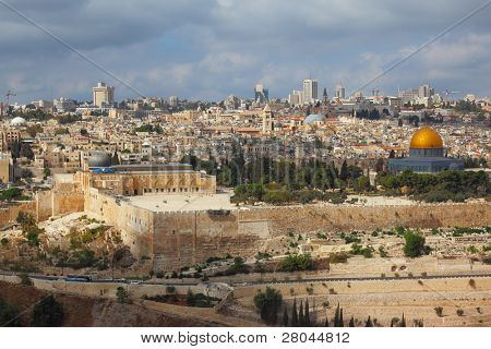 Holy City of Jerusalem. The magnificent panorama of the city. Dome of the Rock, Omar Mosque and the Dome of the Holy Sepulcher. In the background - modern skyscrapers and cranes newly