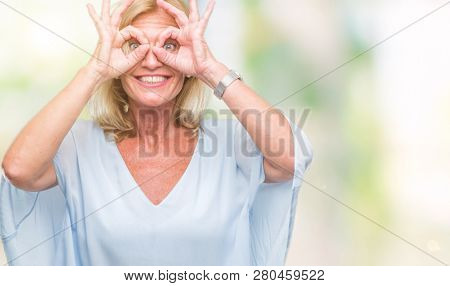 Middle age blonde business woman over isolated background doing ok gesture like binoculars sticking tongue out, eyes looking through fingers. Crazy expression.