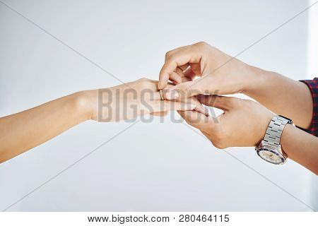 Man Putting Ring On Finger Of Fiance, Isolated On White
