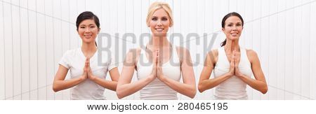 Panoramic web banner interracial group of three beautiful young women hands in prayer practising yoga at a gym or health club poster