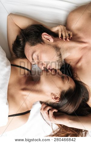 Unshaved man and attractive woman 30s hugging together while lying in bed at home or hotel apartment