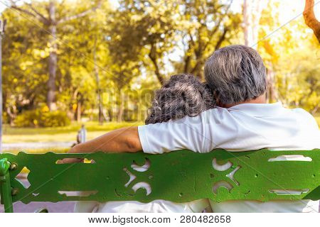 Happy Life And Long Lived Concept. At The End Of Life, Older Couple Sitting Together On Bench At A P