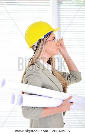 Female engineer with helmet and blueprints at business office