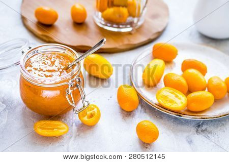 Kumquat On Plate And Jam In Jar At Gray Background