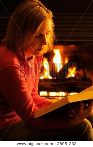 A Mature Woman Reading The Bible By Firelight On A Winters Evening At Home