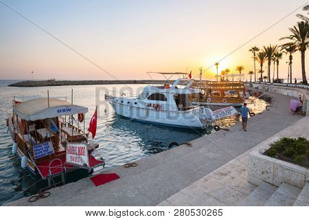 Side, Turkey - June 8, 2018: People at the harbor area of Side town at sunset, Turkey. Side is an ancient Greek city on the southern Mediterranean coast of Turkey.