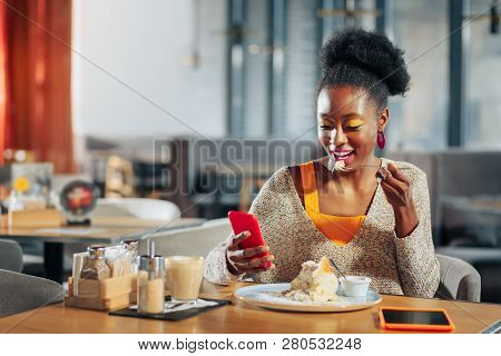 Woman With Bright Makeup Eating Dessert And Reading Message On Phone