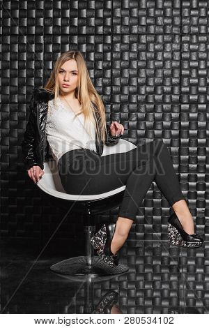 Elegant  Woman Posing On A Chair Near The Wall, Wearing A Jacket, Pants And A White Blouse.