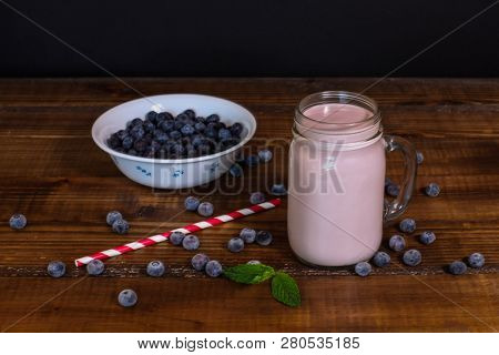 Blueberry smoothie with straw on wooden table