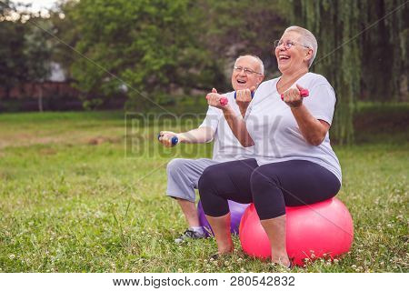 Cardio Exercise For Senior- Smiling Senior Sports Woman And Man Sitting On Fitness Ball With Dumbbel