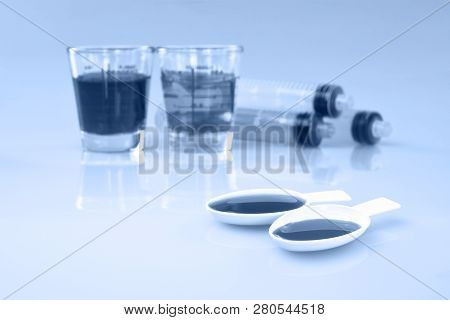 Medicinal Cup, Oral Syring And Teaspoon Filled With Oral Syrup Medicine.
