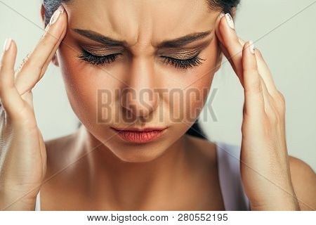 Health And Pain. Stressed Exhausted Young Woman Having Strong Tension Headache. Closeup Portrait Of