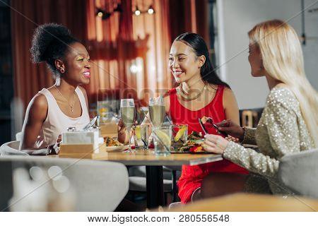 Three Fashionable Women Wearing Stylish Dresses Having Dinner
