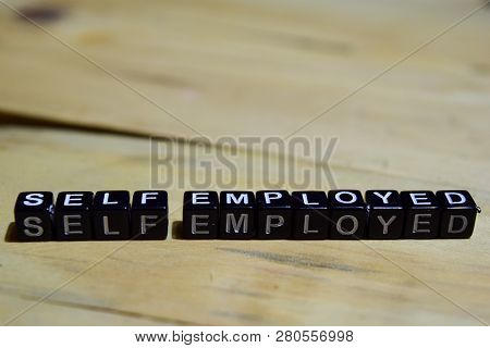 Self Employed Message Written On Wooden Blocks. Education And Motivation Concepts. Cross Processed I