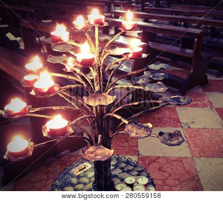 Candlestick With Many Candles Lit By The Faithful Inside A Church As A Sign Of Faith And Devotion