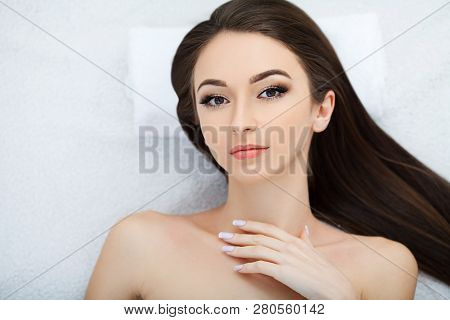 Spa. Young Beautiful Woman Lying On The Bed With Happy Spa Body And Scrub Skin At Spa Salon. Concept