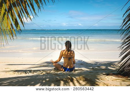 Girl Doing Yoga On Tropical Beach. Young Girl Traveler Relaxing In Vacation.girl In Yoga Position Re