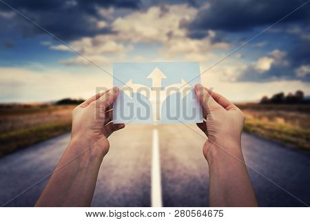 Hands Holding Paper With Arrows Crossroad Symbol Splitted In Three Different Directions. Choose The