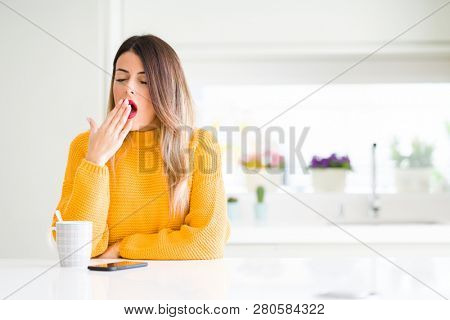 Young beautiful woman drinking a cup of coffee at home bored yawning tired covering mouth with hand. Restless and sleepiness.