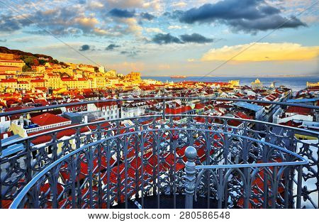 Panorama of Lisbon, Portugal. View from Santa Justa Lift viewing platform at Alfama district old town and sea far away. Evening sunset with dramatic sky. Famous touristic destination landmark.